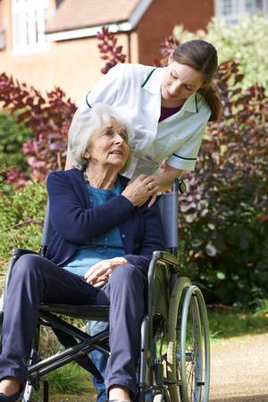 paraplegico: Cuidador empujar a la mujer mayor en silla de ruedas