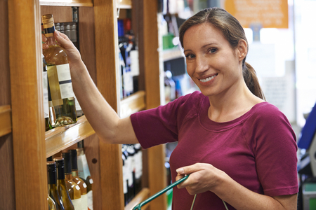 choose person: Woman Choosing Bottle Of White Wine In Supermarket Stock Photo