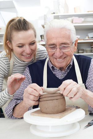 ceramika: Senior Man With Teacher In Pottery Class Zdjęcie Seryjne