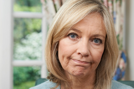 Head And Shoulders Portrait Of Unhappy Mature Woman At Home Stock Photo
