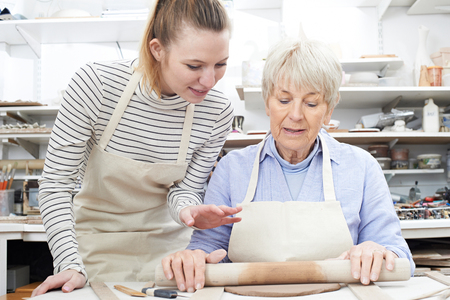 the elderly tutor: Senior Woman Rolling Out Clay With Teacher In Pottery Class