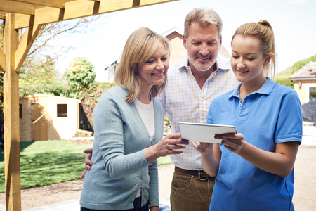 home and garden: Mature Couple Discussing Plans On Digital Tablet With Landscape Gardener Stock Photo