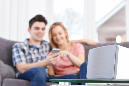 Couple Streaming Music From Mobile Phone To Wireless Speaker