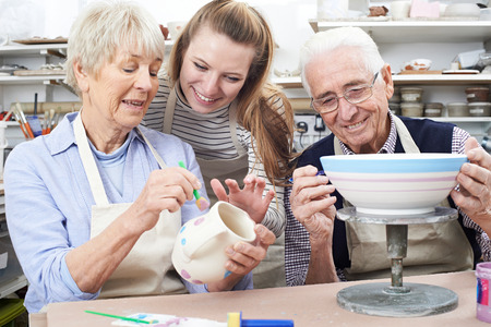 Senior Couple With Teacher In Pottery Class 스톡 콘텐츠