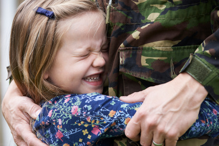 coming home: Soldier On Leave Being Hugged By Daughter Stock Photo