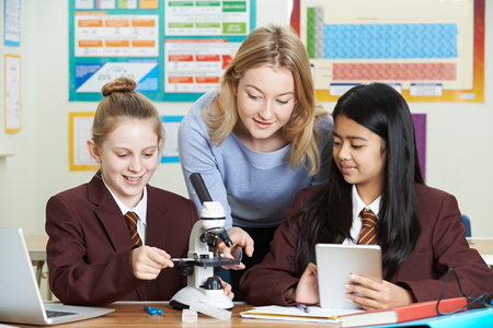Teacher With Female Students Using Microscope In Science Class