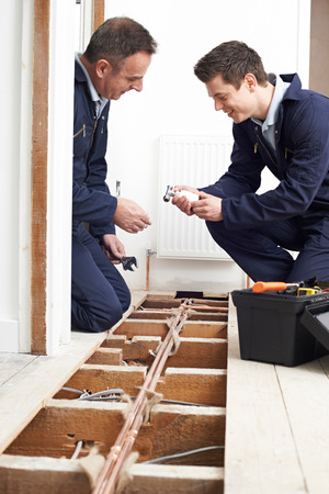 Plumber And Apprentice Fitting Central Heating in House Stock Photo