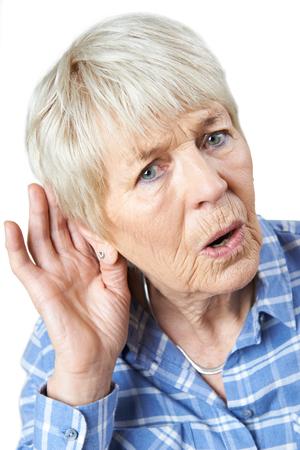 straining: Studio Shot Of  Senior Woman Suffering From Deafness Stock Photo