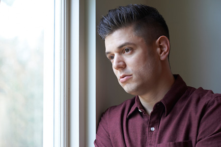 man looking out: Sad Man Suffering From Depression Looking Out Of Window