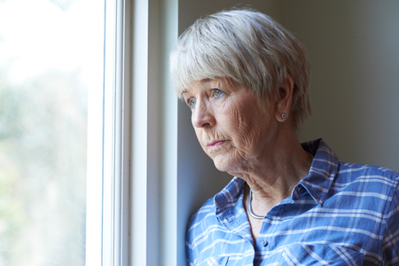 Senior Woman Suffering From Depression Looking Out Of Window