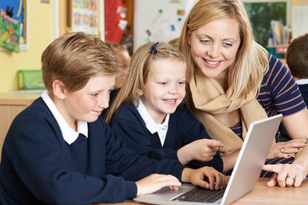 uniformes: Profesor de ayuda a la Escuela Primaria Los alumnos en clase del ordenador