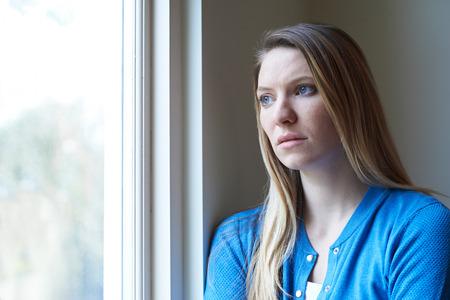 Sad Woman Suffering From Depression Looking Out Of Window Banque d'images