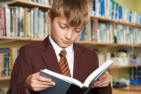 Boy Wearing School Uniform Reading Book In Library Stock Photo