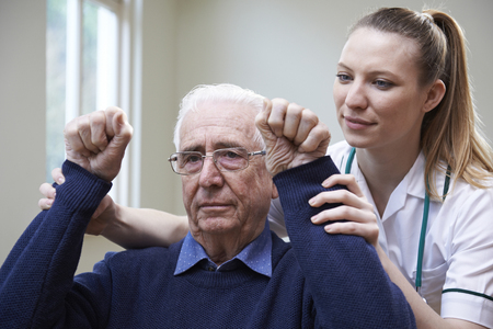Nurse Assessing Stroke Victim By Raising Arms Stock Photo