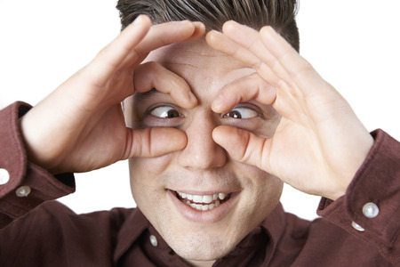 near sighted: Studio Shot Of Man Making Spectacle Shape With His Hands Stock Photo