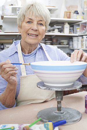 Senior Woman Decorating Bowl In Pottery Class