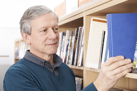 borrowing: Mature Male Student Studying In Library Stock Photo