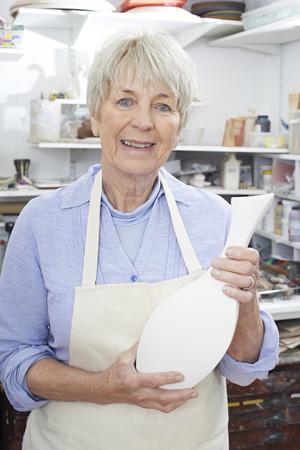 the elderly tutor: Portrait Of Senior Woman Holding Vase In Pottery Studio