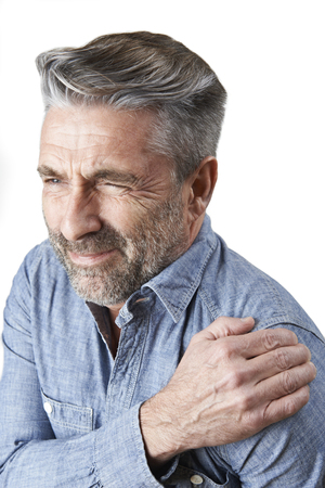 Studio Shot Of Man Suffering With Frozen Shoulder Archivio Fotografico