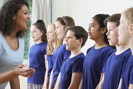 Group Of Children With Teacher Enjoying Singing Group Stock Photo