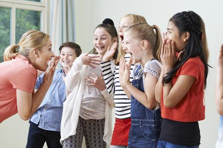 Group Of Children With Teacher Enjoying Drama Class Together Archivio Fotografico