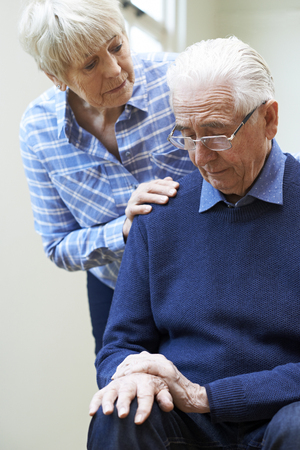Senior Woman Comforts Husband Suffering With Parkinsons Diesease