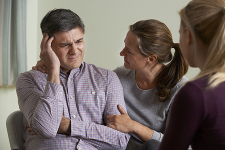 Mature Couple Talking With Counsellor As Woman Comforts Man photo