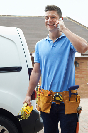 Electrician With Van Talking On Mobile Phone Outside House Stock Photo