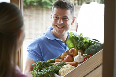 Man Making Home Delivery Of Organic Vegetable Box Stock Photo - 79619793
