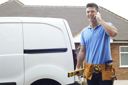 Builder With Van Talking On Mobile Phone Outside House