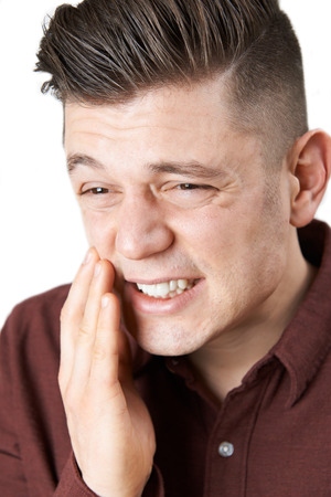 Studio Shot Of Young Man Suffering With Toothache