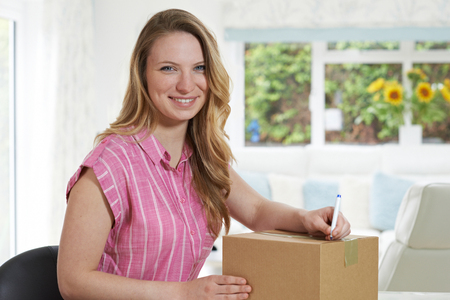 addressing: Portrait Of Woman At Home Writing Address On Package