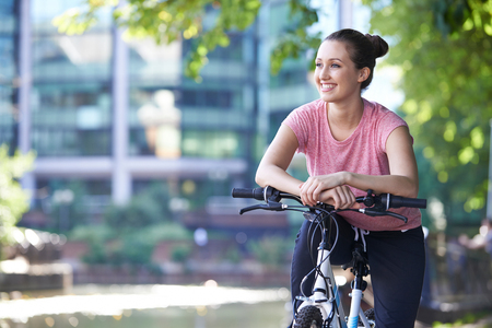 Young Woman Cycling Next To River In Urban Setting