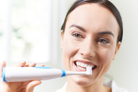 Woman Brushing Teeth With Electric Toothbrush In Bathroom Stock Photo