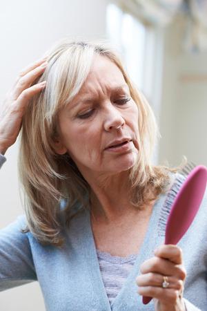 Mujer madura con el cepillo Corncerned sobre pérdida del pelo Foto de archivo - 81919712