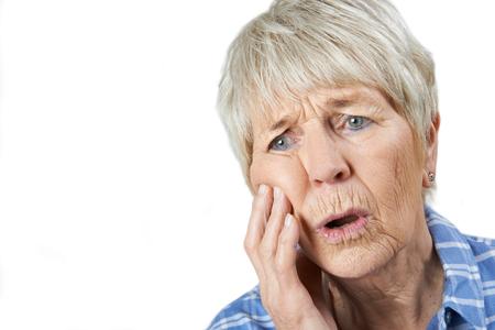 Studio Portrait Of Senior Woman Suffering With Toothache Stock Photo