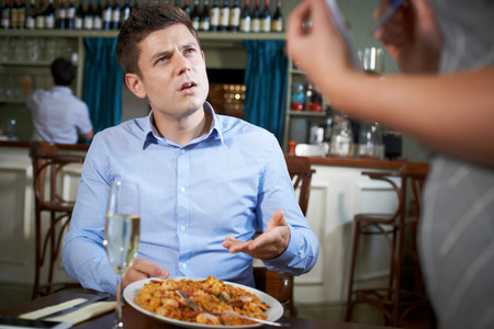 Customer In Restaurant Complaining To Waitress About Food