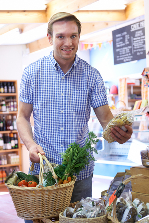 shopper: Male Shopper In Delicatessen Buying Organic Produce