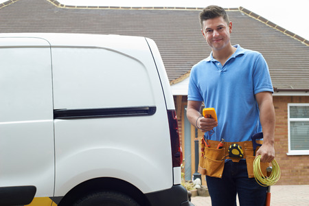 Portrait Of Electrician With Van Outside House Stock Photo