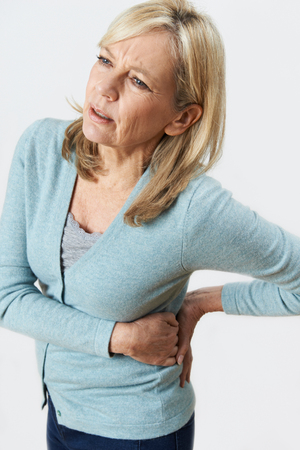 Studio Shot Of Mature Woman Suffering With Kidney Pain Banque d'images