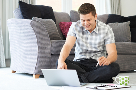 Male Freelance Worker Using Laptop At Home