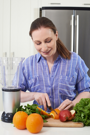 Woman In Kitchen Chopping Fruit To Put Into Juicer Banque d'images