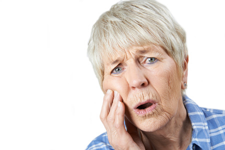 Studio Portrait Of Senior Woman Suffering With Toothache Stock Photo