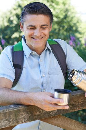 Mature Man Pouring Hot Drink From Flask On Walk Banque d'images