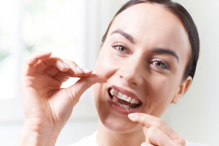 Woman  In Bathroom Flossing White Teeth Banque d'images