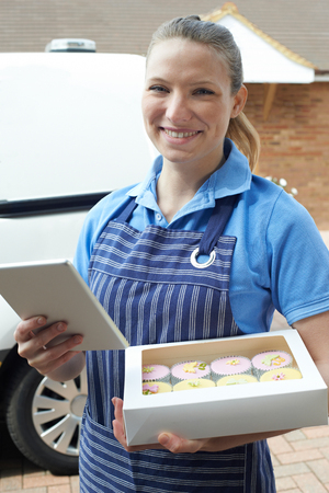 Female Baker With Digital Tablet Making Home Delivery Of Cupcakes