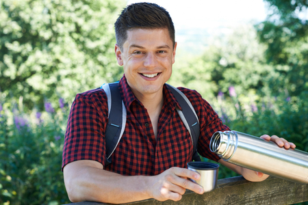 Portrait Of Man Pouring Hot Drink From Flask On Walk