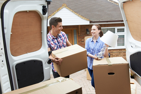 Young Couple Moving In To New Home  Unloading Removal Van Banque d'images