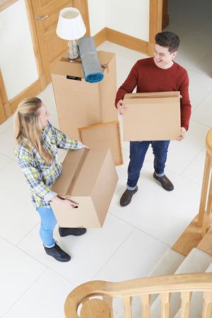 Jeune couple portant des boîtes en mouvement en journée