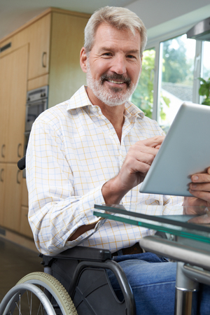 Portrait Of Disabled Man In Wheelchair Using Digital Tablet At Home Banque d'images